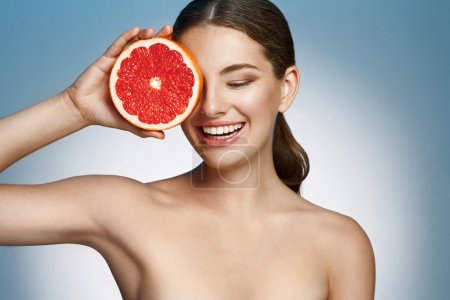 Photo for Photoset of attractive girl holding a cut piece of Sicilian orange on blue background - Royalty Free Image