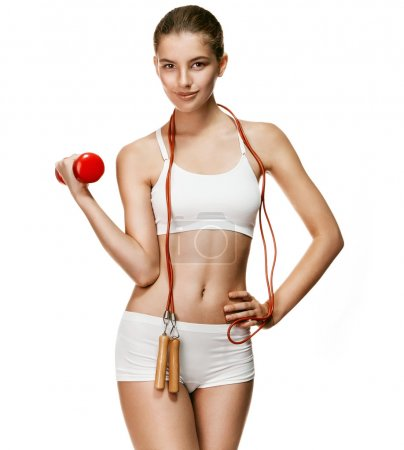 Likeable fit girl with red dumbbell and skipping rope, jumping-rope