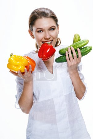 Cheerful young woman of the European appearance promotes a healthy lifestyle by eating health food