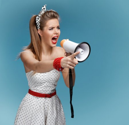 Angry pin-up girl shouting into a megaphone, mouthpiece, speaking trumpet. Filmmaking or film production concept