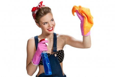 Beautiful worker wearing pink rubber protective gloves holding cleaning spray bottle and orange microfiber cloth