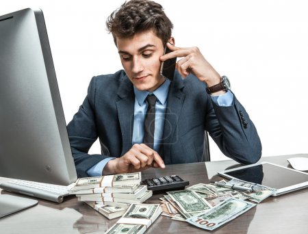 Successful businessman going to make a call by cellphone while working with PC computer and calculator