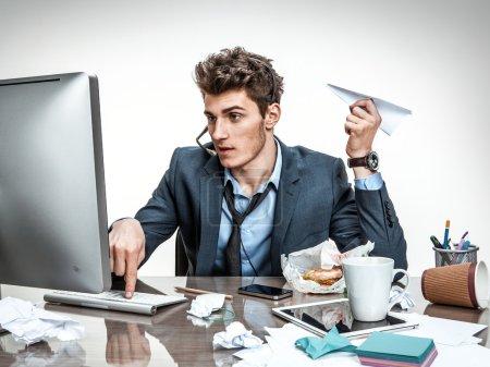 Photo pour Employé de bureau avec avion de papier à la main en tapant sur un clavier d'ordinateur - image libre de droit
