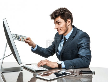 Young man inserting a dollar into a monitor, paying online concept