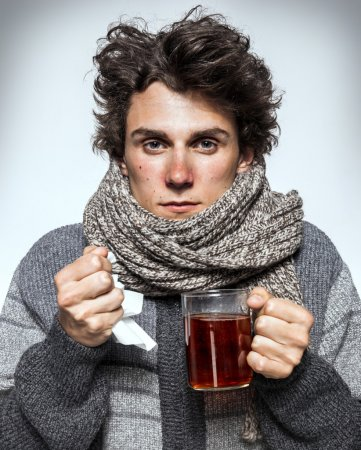 Ill young man with red nose, scarf, sneezing into handkerchief.