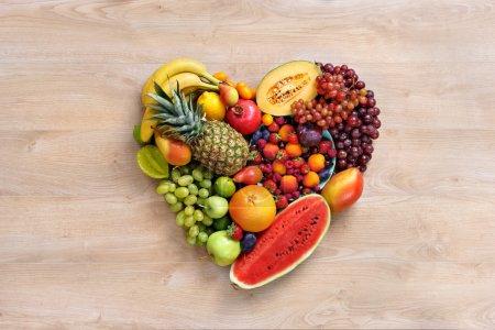 Foto de Símbolo del corazón. Concepto de dieta de frutas. Saludable comer concepto / fotografía de comida de corazón de diferentes frutas en mesa de madera. Producto de alta resolución. - Imagen libre de derechos