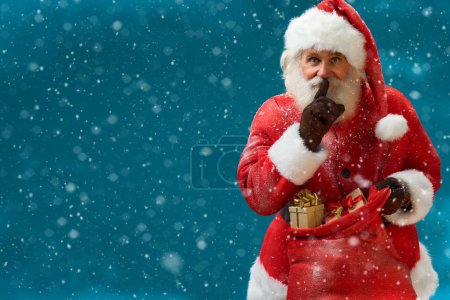 Santa Claus with huge red sack keeping forefinger by his mouth and looking at camera / Merry Christmas & New Year's Eve concept / Closeup on blurred blue background.