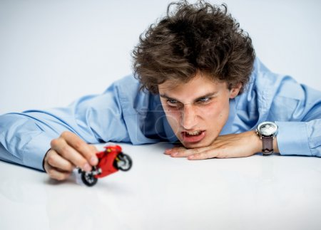 Irritable office worker plays with toy motorbike