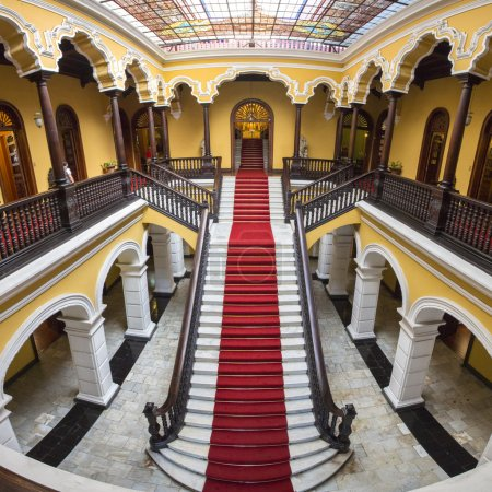 Photo for Yellow colonial interior and marble staircase with red carpet at Archbishop's Palace in Lima during the day, Peru - Royalty Free Image