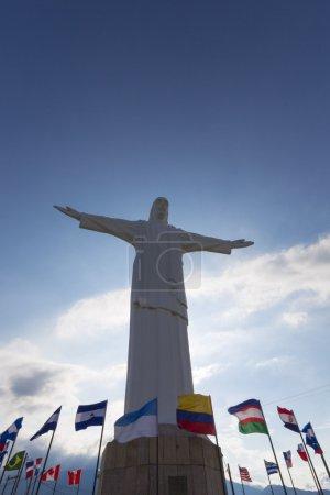 Photo pour Vue de face de la statue de Cristo del Rey de Cali contre un ciel bleu avec des drapeaux internationaux agitant autour. Colombie - image libre de droit