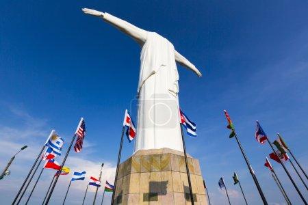 Photo pour Vue arrière de la statue de Cristo del Rey de Cali contre un ciel bleu avec des drapeaux internationaux agitant autour. Colombie - image libre de droit