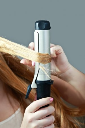 woman using curling iron on her hair