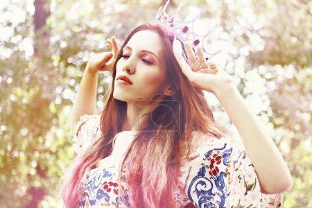 Boho princess in white crown with sad expression o...
