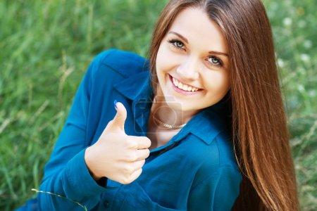 Photo pour Portrait de jeune femme belle avec heureusement soulève pouce vers le haut et souriant, sur la nature de fond vert été. - image libre de droit
