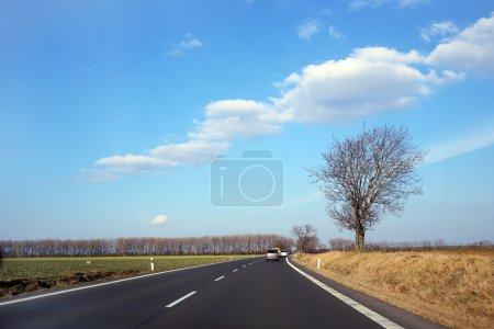 Photo pour Route asphaltée à horizon sous le ciel bleu - image libre de droit