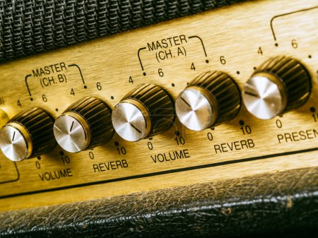 Photo for Macro photo of a vintage electric guitar amplifier focusing on the volume knob which is set at ten. - Royalty Free Image