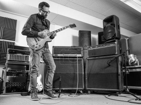 Photo pour Photo d'un homme dans sa position de fin de la vingtaine d'enregistrement en studio jouant de sa guitare électrique. - image libre de droit