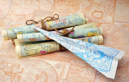 old rolled maps and paper airplane