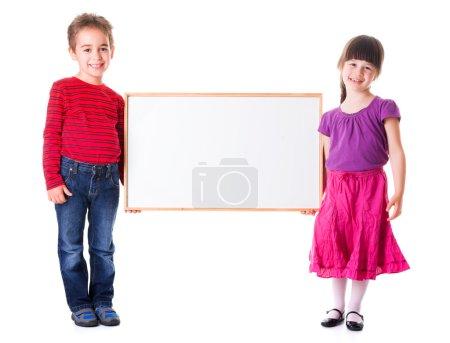 Photo pour Mignon fille et garçon tenant tableau publicitaire vierge - image libre de droit