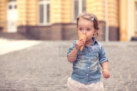 Tiny girl eating ice cream on street