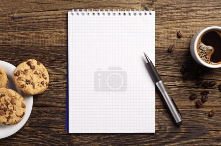 Notepad and coffee with cookies