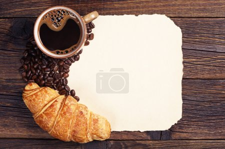 Photo for Croissant and cup of hot coffee and blank sheet of old paper as a background, top view - Royalty Free Image