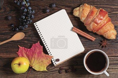 Foto de Croissant con bloc de notas abierto, café y frutas en la mesa de madera oscura, vista superior - Imagen libre de derechos