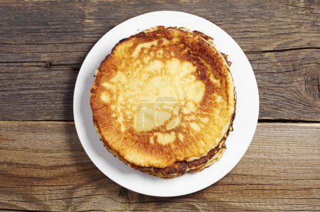 Photo for Fried pancakes in plate on rustic wooden table, top view - Royalty Free Image