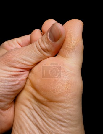 Thumb pressure on big toe massage on dry skin isolated towards b