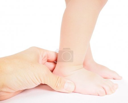 Photo for Male hand holding firmly around a foot of toddler isolated on white - Royalty Free Image