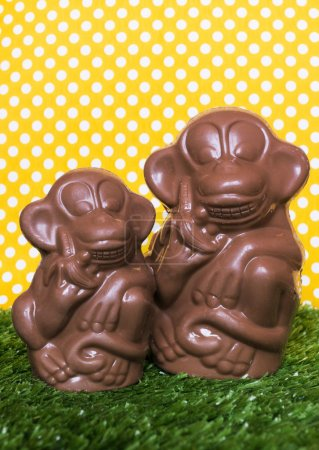 Photo for The chocolate figures of monkeys on the green grass. The monkey is a symbol of New Year. - Royalty Free Image