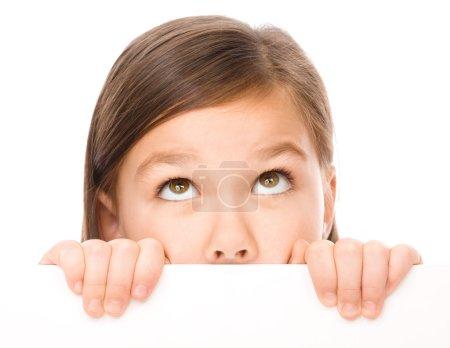 Photo pour Petite fille regarde à partir du tableau blanc, isolé sur blanc - image libre de droit