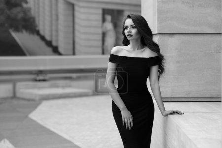 Photo pour Portrait noir et blanc de jeune belle femme élégante en robe noire. Jolie fille sensuelle avec de longs cheveux bouclés posant à l'extérieur à la rue de la ville - image libre de droit