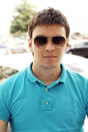 Photo for Outdoor portrait of young handsome man in sunglasses and polo shirt - Royalty Free Image