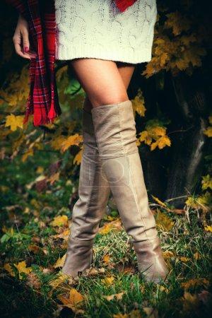 Photo pour Femme portant une robe blanche en laine, une écharpe en tartan rouge et de longues bottes en cuir, prise de vue en plein air dans le parc d'automne - image libre de droit