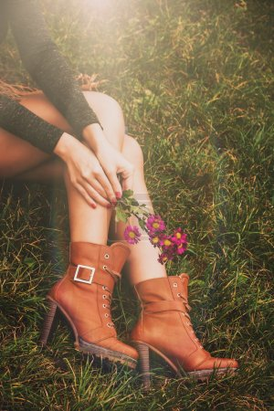 Photo pour Woman legs in brown ankle high heel boots sit on grass hold flowers in hands - image libre de droit