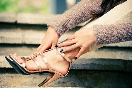Foto de Piernas de mujer en tacón alto sandalias de oro se inclinan en las escaleras, tiro al aire libre, de cerca - Imagen libre de derechos