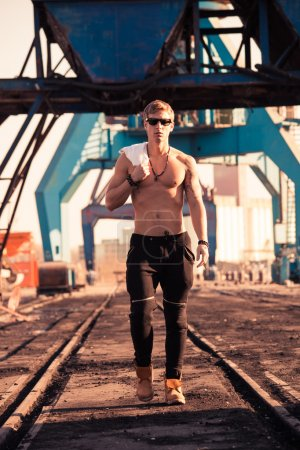 Photo pour Jeune homme blond beau torse nu marchant dans le port - image libre de droit