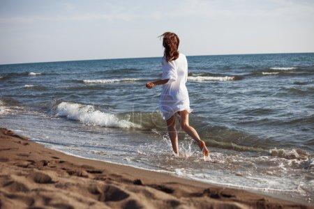 Photo pour Femme aux pieds nus dans les chemise blanche traversent l'eau de mer sur la plage de sable fin, retour, avis, corps entier tourné - image libre de droit
