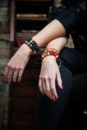 Foto de Manos de mujer con pulseras de apoyan en las piernas tiro interior - Imagen libre de derechos