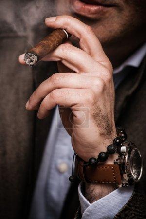 Photo pour Homme élégant portant costume et chemise blanche fumeur tir intérieur de cigare, closeup, mise au point sélective - image libre de droit