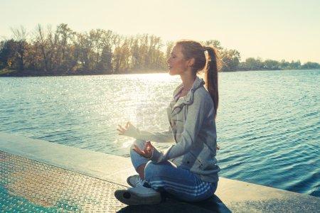 Woman meditate on lake