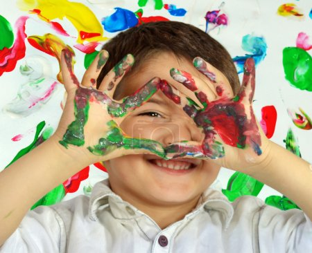 Photo for Little boy painting with hands with different color paint on his palms - Royalty Free Image