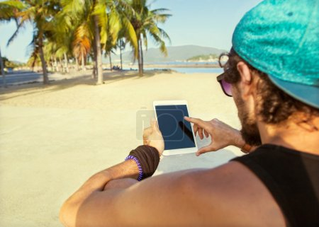 freelancer working guy sitting on the beach with views of palm t