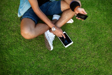 Outdoor portrait of modern young man with mobile phone, tablet o