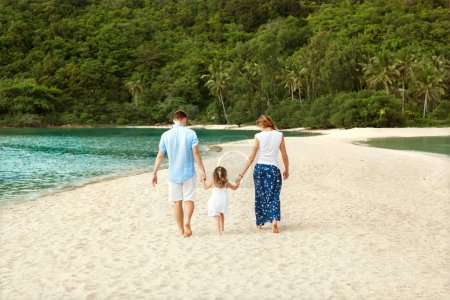 Photo for Happy family walking on the sea on the beach - Royalty Free Image