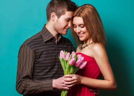 Portrait of young couple in love with flowers tulips posing at s
