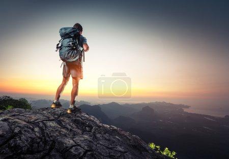 Photo pour Randonneur avec sac à dos debout au sommet d'une montagne et profitant du lever du soleil - image libre de droit