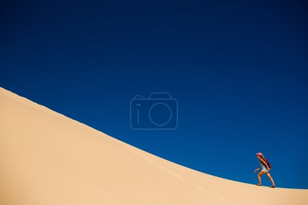 Hiker climbing the dune