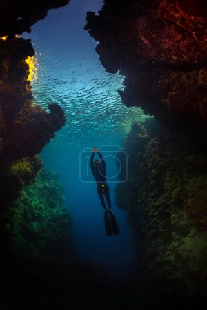 Free diver gliding in the cave
